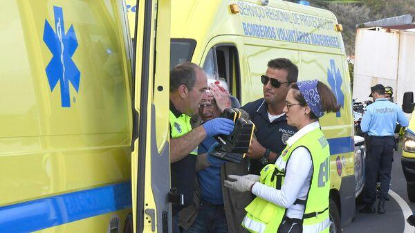 Медики оказывают помощь пострадавшему в результате ДТП с туристическим автобусом в Португалии. 17 апреля 2019
