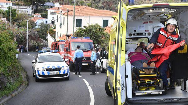 Автомобили скорой помощи и полиции вокруг места аварии с участием туристического автобуса в Португалии