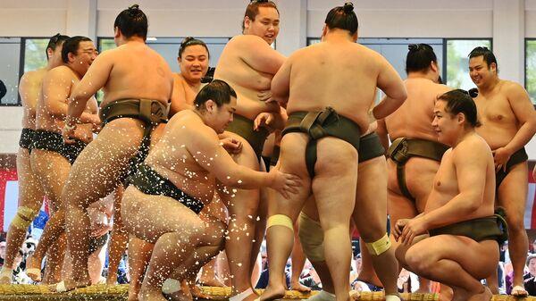 Борцы сумо в ожидании начала ежегодного церемониального турнира по сумо Honozumo в Токио, Япония
