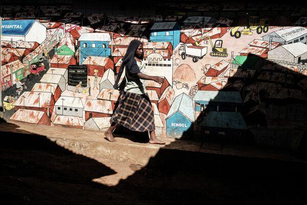 Женщина идет вдоль стены с граффити в Кибере, Найроби