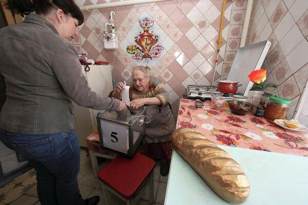 Женщина опускает бюллетень в мобильную урну для голосования в одном из домов в Харьковской области во время второго тура президентских выборов на Украине