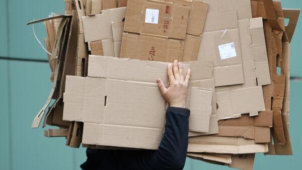 Мужчина несет картонные коробки