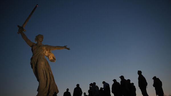 Посетители у скульптуры Родина-мать зовет! на территории Историко-мемориального комплекса Героям Сталинградской Битвы на Мамаевом Кургане