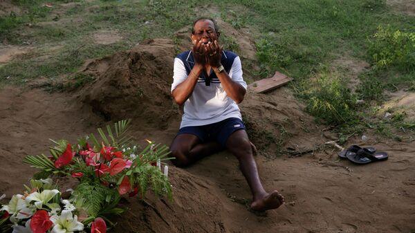 Мужчина скорбит рядом с могилой родственника, погибшего во время взрывов в пасхальное воскресенье в Негомбо, Шри-Ланка. 23 апреля 2019