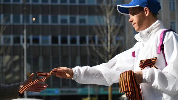 Волонтер раздает георгиевские ленточки на Зубовском бульваре в Москве