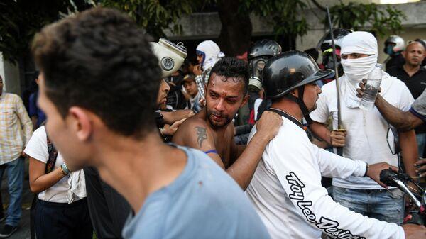 Одного из протестующих, раненного во время столкновения с Национальной гвардией Венесуэлы в Альтамире, районе Каракаса, увозят на мотоцикле