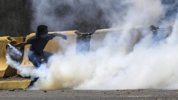 Протестующий кидает бутылку со слезоточивым газом во время столкновения с Национальной гвардией Венесуэлы в Альтамире, районе Каракаса