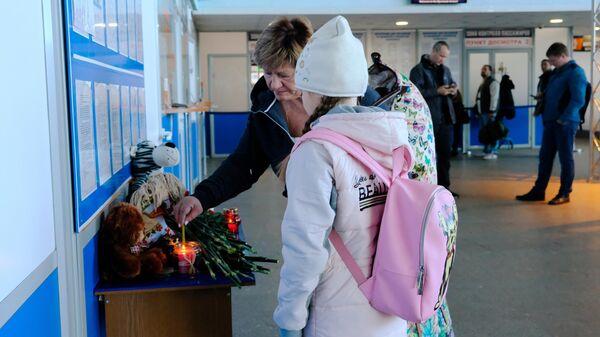 Пассажиры зажигают свечу  в аэропорту Мурманска в знак траура по жертвам катастрофы самолета Аэрофлота