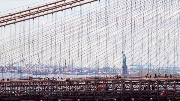 Вид на Стасую Свободы сквозь Бруклинский мост в Нью-Йорке