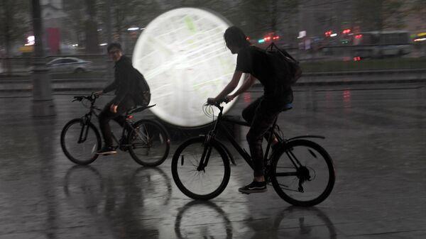 Велосипедисты во время дождя на одной из улиц в Москве