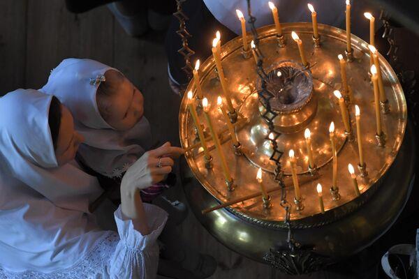 Прихожане зажигают свечи в день праздника Святых Жён-Мироносиц в одном из храмов духовного центра старообрядчества Рогожская слобода в Москве
