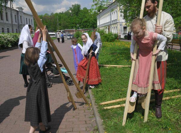 Участники развлечений на ходулях в день праздника Святых Жён-Мироносиц в духовном центре старообрядчества Рогожская слобода в Москве
