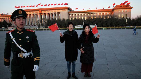 Женщины позируют с национальными флагами на площади Тяньаньмэн в Пекине