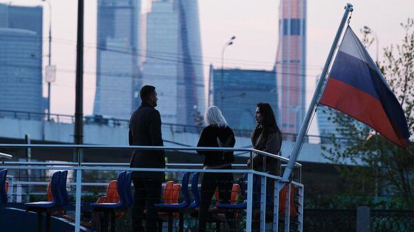 Люди на палубе теплохода во время прогулки по Москве-реке. На втором плане: небоскребы делового центра Москва-сити