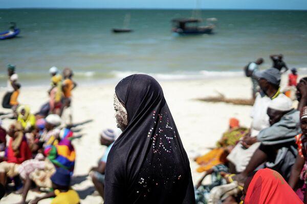 Женщина на пляже ожидает помощи после разрушительного циклон на острове Мозамбика
