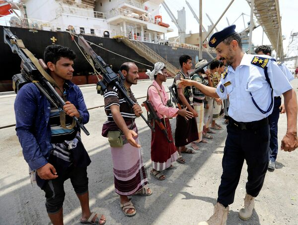 Офицер береговой охраны Йемена пожимает руки хуситам во время вывода из порта Салеф в провинции Ходейда