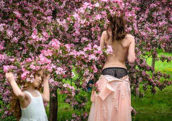 Девушка позирует во время фотосессии в вишневом саду в парке Коломенское в Москве
