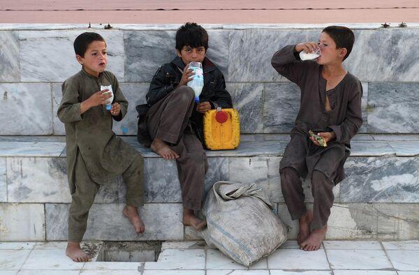 Афганские мальчики с питьевыми йогуртами во внутреннем дворе Голубой мечети во время священного месяца Рамадан в Мазари-Шарифе