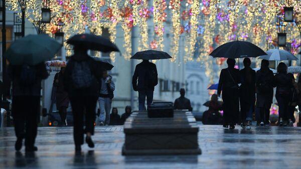 Прохожие на одной из улиц Москвы во время дождя