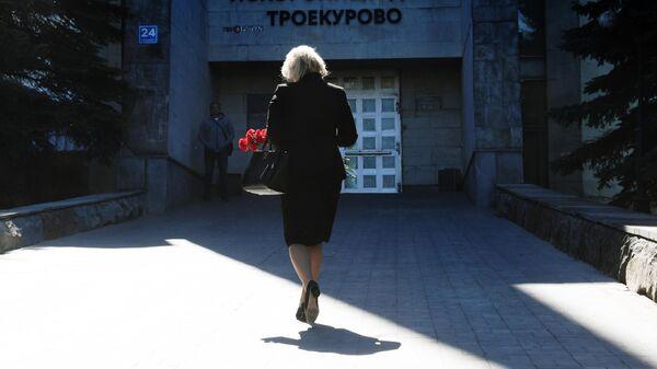 Женщина с цветами идет на церемонию прощания с главным редактором радиостанции Говорит Москва Сергеем Доренко