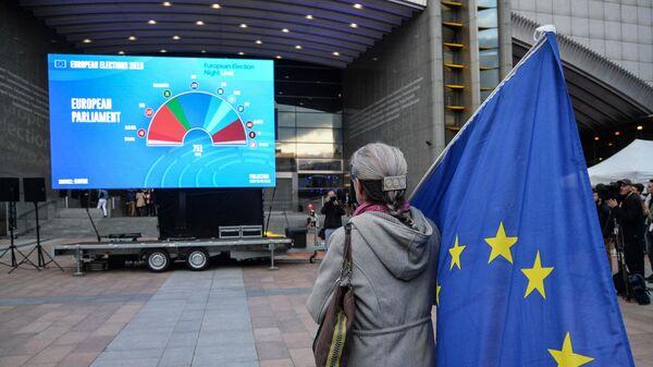 Женщина с флагом ЕС у штаб-квартиры Европпарламента в Брюсселе