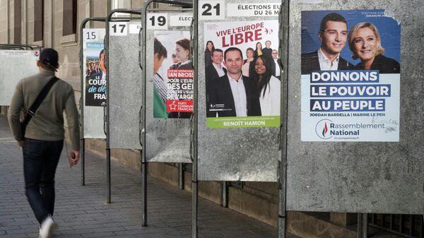 Предвыборные плакаты кандидатов в заключительный день голосования на выборах в Европейский парламент (ЕП) у избирательного участка в Париже