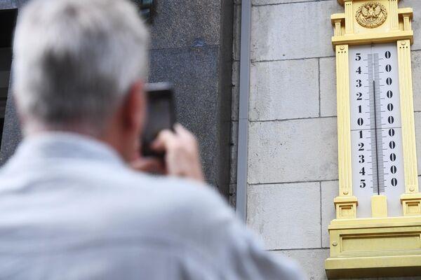 Мужчина фотографирует термометр на здании Государственной Думы РФ в Москве