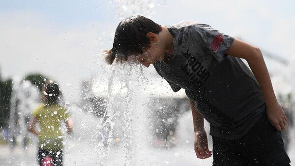 Молодой человек ополаскивает голову в фонтане в парке искусств Музеон
