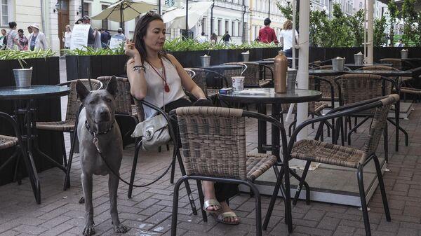 Посетительница с собакой на летней веранде кафе на улице Арбат в Москве