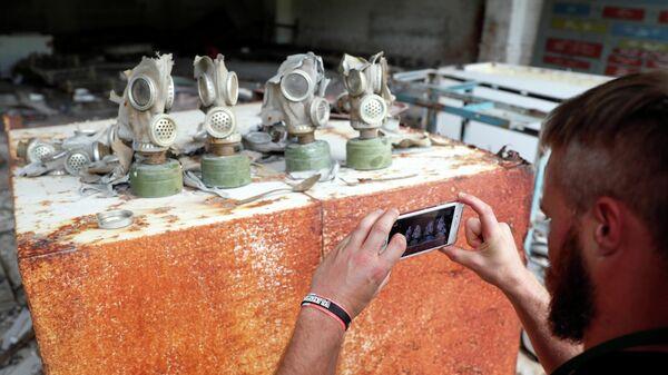 Турист фотографирует противогазы на бывшей базе советской армии, недалеко от Чернобыльской АЭС, Украина