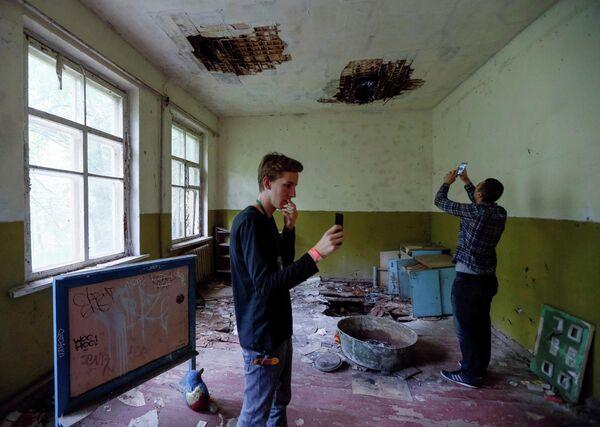 Туристы фотографируются в детском саду в заброшенном поселке Копачи, недалеко от Чернобыльской АЭС, Украина