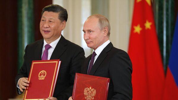 Президент РФ Владимир Путин и председатель Китайской Народной Республики Си Цзиньпин на церемонии подписания совместных документов по итогам российско-китайских переговоров в Кремле