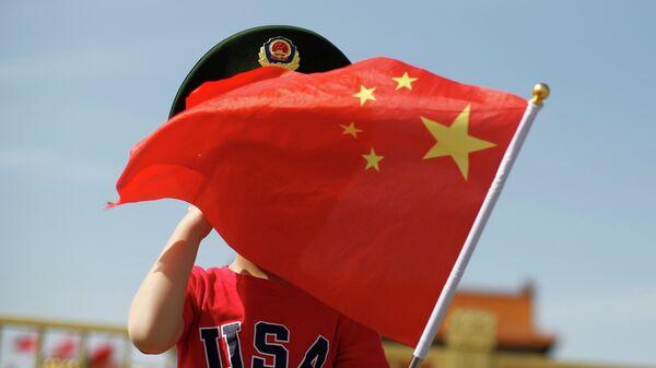 Мальчик в футболке с надписью США машет национальным флагом Китая на площади Тяньаньмэнь в Пекине