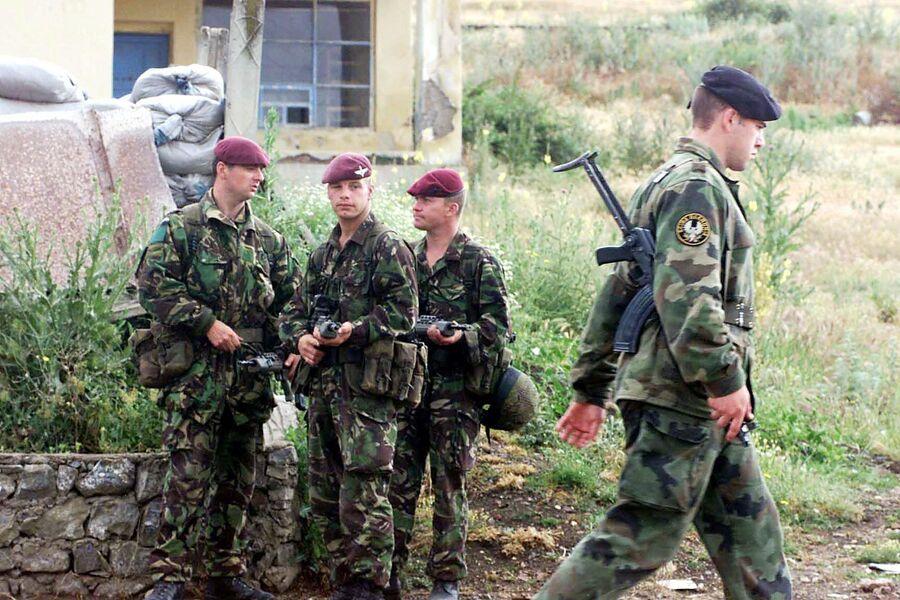 Солдат югославской армии проходит мимо солдат 1-й воздушно-десантной дивизии Великобритании по дороге к аэропорту Приштины