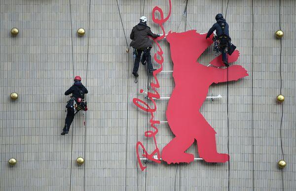 Промышленные альпинисты устанавливают фигуру медведя на кинотеатре в Берлине