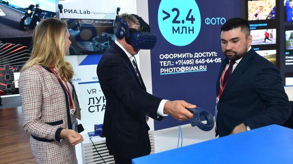 Заместитель председателя Государственной корпорации развития ВЭБ.РФ Алексей Сорокин тестирует очки виртуальной реальности проекта РИА.Lab на стенде МИА Россия сегодня