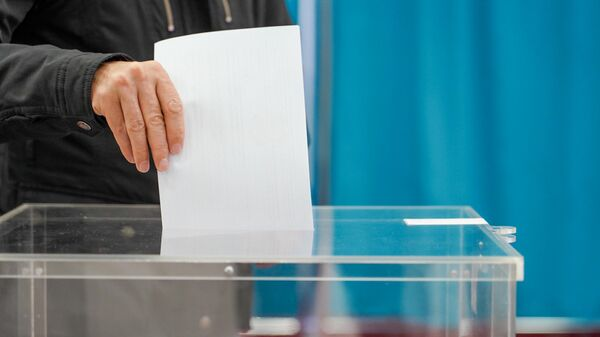 Мужчина опускает бюллетень в урну для голосования на внеочередных выборах президента Казахстана во Дворце школьников в Нур-Султане. 9 июня 2019