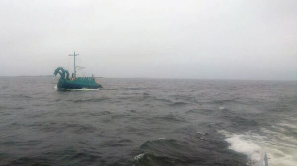Вид на Российскую яхту в стиле древнерусской ладьи Змей Горыныч с борта судна Финской береговой охраны
