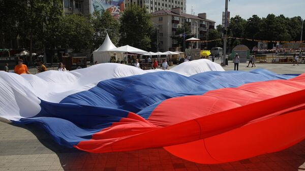 Участники флэшмоба Я люблю Россию развертывают огромный триколор на Главной городской площади в Краснодаре