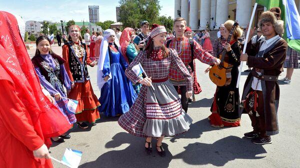 Молодые люди в национальных костюмах на праздновании Дня России в Челябинске