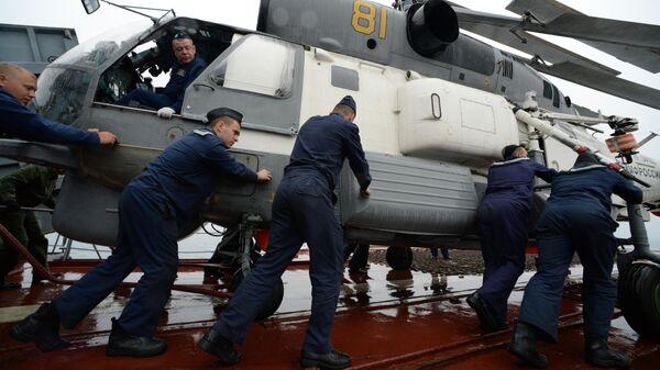 Моряки готовят к полёту вертолёт Ка-27 во время совместных российско-японских учений по поиску и спасению на море Сарекс-2019