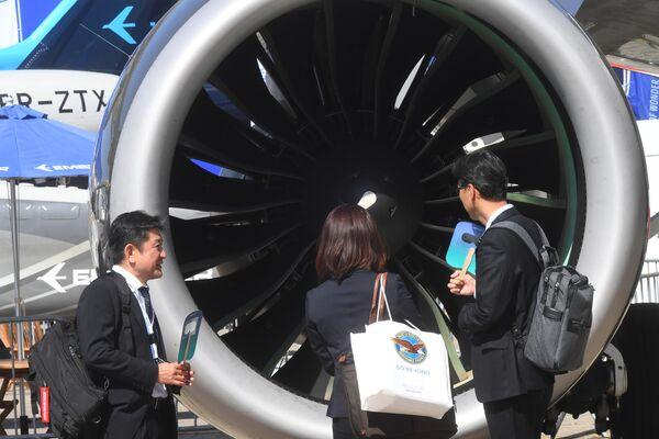 Посетители осматривают турбину самолета на международном аэрокосмическом салоне Paris Air Show 2019 во Франции