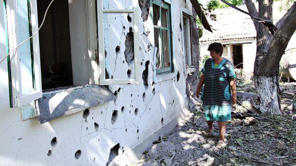 Женщина у жилого дома в поселке Новая Марьевка в Донецкой области, пострадавшего в результате ночного обстрела