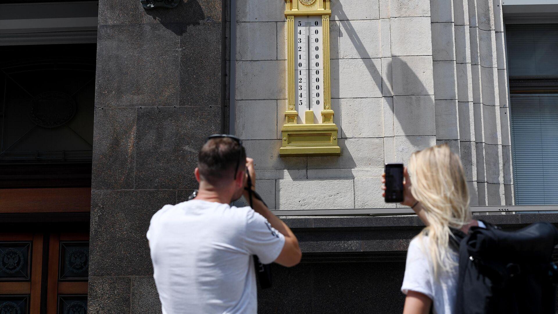 Молодые люди фотографируют термометр на здании Государственной Думы РФ в Москве - РИА Новости, 1920, 13.04.2021
