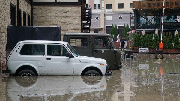 Автомобили на затопленной улице на горнолыжном курорте Роза Хутор. 24 июня 2019