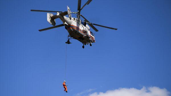 Спасатель-медик спускается на тросе с вертолета Ка-32А МАЦ во время учений