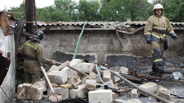 Сотрудники МЧС ДНР устраняют завалы в помещении гаража, полученные в результате артиллерийского обстрела Петровского района Донецка. 25 июня 2019