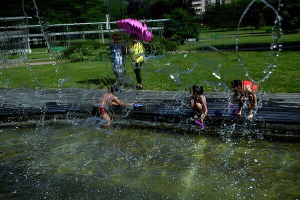 Люди купаются в фонтане в Памплоне, Испания