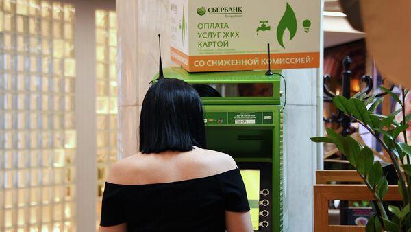 Девушка оплачивает коммунальные платежи в банкомате Сбербанка