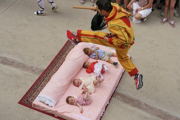 Мужчина перепрыгает через детей во время фестиваля Сальто-дель-Колачо